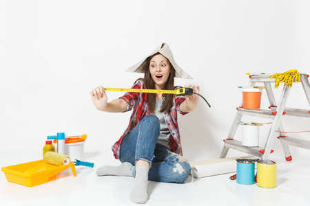 Pretty woman in newspaper hat sitting on floor with measure tape, instruments for renovation apartment isolated on white background. Wallpaper, gluing accessories, painting tools. Repair home concept Reklamní fotografie