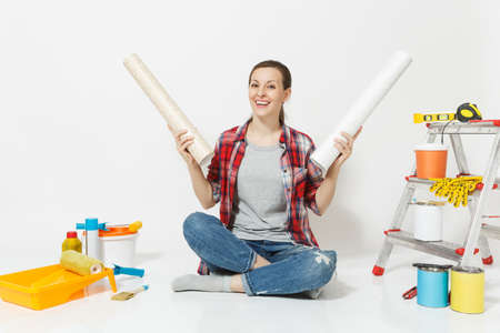 Woman in casual clothes sitting on floor with wallpaper rolls instruments for renovation apartment isolated on white background. Accessories for gluing painting tools. Repair home concept. Copy space Reklamní fotografie
