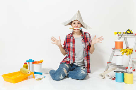 Woman in newspaper hat sitting on floor with brush in mouth, instruments for renovation apartment isolated on white background. Wallpaper, accessories for gluing, painting tools. Repair home concept