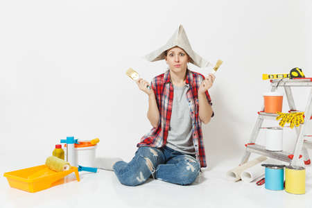 Fun woman in newspaper hat sitting on floor with brush, instruments for renovation apartment room isolated on white background. Wallpaper, accessories for gluing, painting tools. Repair home concept