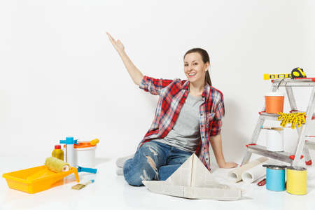 Pretty woman pointing hand aside on copy space, sit on floor with newspaper hat, instruments for renovation apartment isolated on white background. Stock Photo