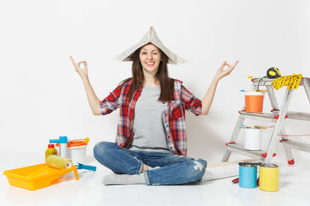 Happy woman in newspaper hat sitting on floor meditating, doing yoga, relaxing with instruments for renovation apartment room isolated on white background.