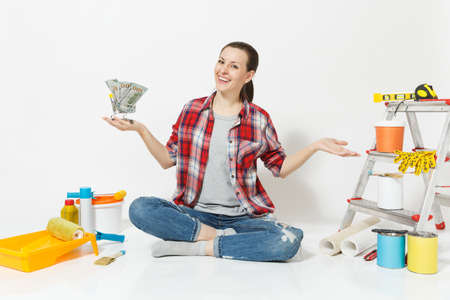 Woman holds bundle of cash money, supermarket grocery push cart for shopping. Instruments for renovation apartment isolated on white background. Wallpaper accessories for gluing Concept repair home