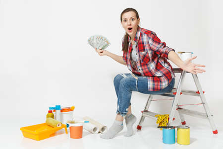 Woman holds bundle of dollars, cash money, sits on ladder with instruments for renovation apartment isolated on white background. Wallpaper accessories for gluing painting tools. Repair home concept Stockfoto