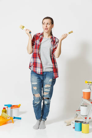 Full length portrait of fun cute woman with brush standing near instruments for renovation apartment home isolated on white background.