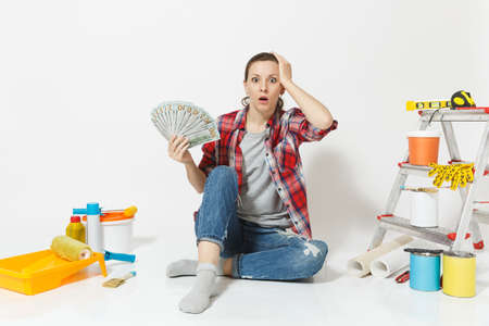 Woman in shock holds bundle of dollars, cash money, sits on floor with instruments for renovation apartment isolated on white background. Wallpaper accessories for gluing tools Concept of repair home