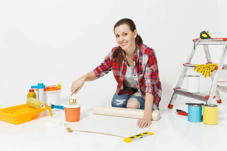 Woman in casual clothes sitting on floor with wallpaper rolls, brush, instruments for renovation apartment isolated on white background. Stockfoto