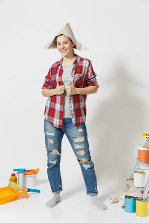 Full length portrait of woman in newspaper hat standing near instruments for renovation apartment room isolated on white background. Wallpaper, accessories for gluing, painting tools. Repair concept Stockfoto