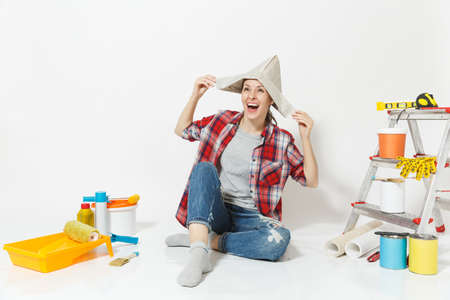 Happy fun woman in newspaper hat sitting on floor with instruments for renovation apartment room isolated on white background. Wallpaper, accessories for gluing, painting tools. Repair home concept