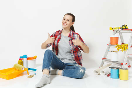Woman in casual clothes show thumbs up, sit on floor with instruments for renovation apartment room isolated on white background. Wallpaper, accessories for gluing, painting tools. Concept of repair