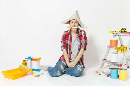 Woman in newspaper hat sitting on floor with brush in mouth, instruments for renovation apartment isolated on white background.