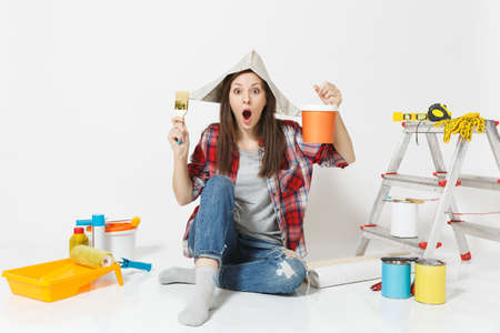 Woman in newspaper hat sitting on floor with brush, paint can, instruments for renovation apartment isolated on white background. Wallpaper accessories for gluing, painting tools. Repair home concept
