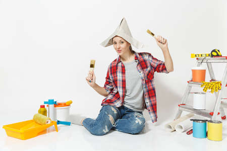 Fun woman in newspaper hat sitting on floor with brush, instruments for renovation apartment room isolated on white background.