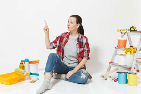 Woman pointing index finger aside on copy space, sit on floor with instruments for renovation apartment isolated on white background. Wallpaper accessories for gluing painting tools Concept of repair Reklamní fotografie