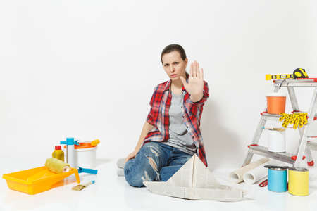 Strict woman sitting on floor with newspaper hat, instruments for renovation apartment room, showing stop gesture with palm isolated on white background. Stock Photo