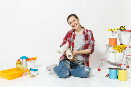 Woman in casual clothes sitting on floor with wallpaper rolls instruments for renovation apartment isolated on white background. Accessories for gluing painting tools. Repair home concept. Copy space Stock Photo