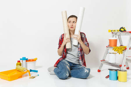 Angry screaming mad woman sitting on floor with wallpaper rolls, instruments for renovation apartment isolated on white background. Accessories gluing, painting tools. Repair home concept. Copy space