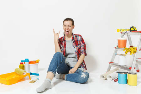 Woman in casual clothes with horns gesture on floor with instruments for renovation apartment room isolated on white background. Wallpaper, accessories for gluing, painting tools. Concept of repair