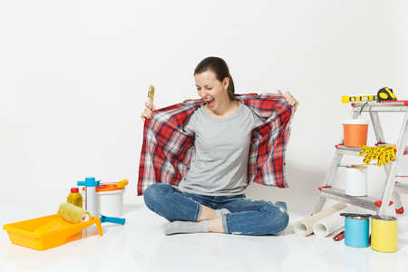 Fun woman in casual clothes sitting on floor with brush, instruments for renovation apartment room isolated on white background. Wallpaper, accessories for gluing, painting tools. Repair home concept