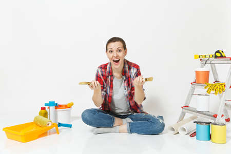Pretty woman in casual clothes sitting on floor with brush, instruments for renovation apartment room isolated on white background.
