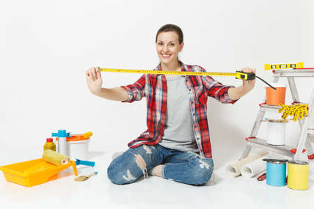 Woman in casual clothes sitting on floor with measure tape, instruments for renovation apartment isolated on white background. Wallpaper, accessories for gluing, painting tools. Repair home concept