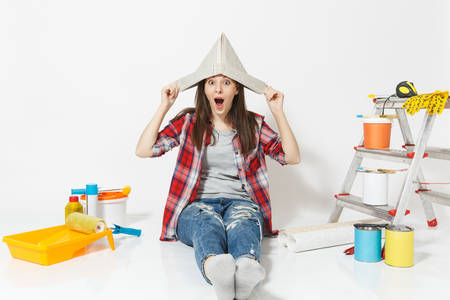 Beautiful fun woman in newspaper hat sitting on floor with instruments for renovation apartment room isolated on white background. Wallpaper, gluing accessories, painting tools. Repair home concept Reklamní fotografie