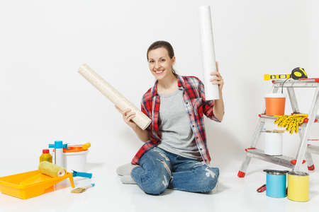 Woman in casual clothes sitting on floor with wallpaper rolls instruments for renovation apartment isolated on white background.