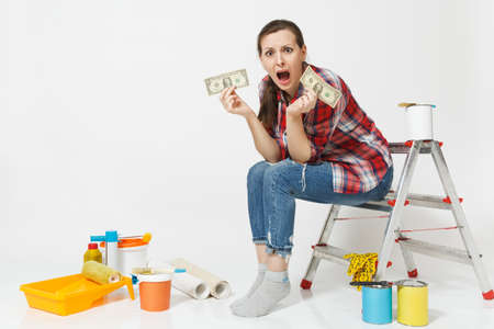 Upset female holds tight of dollars, cash few money, sits on ladder with instruments for renovation apartment isolated on white background. Wallpaper gluing accessories painting tools. Repair concept