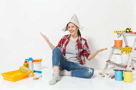 Woman in newspaper hat spreading hands, sitting on floor with instruments for renovation apartment isolated on white background. Wallpaper, accessories for gluing, painting tools. Repair home concept Reklamní fotografie
