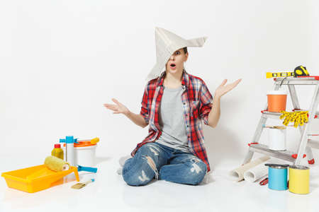 Shocked fun woman in newspaper hat sitting on floor with instruments for renovation apartment room isolated on white background.