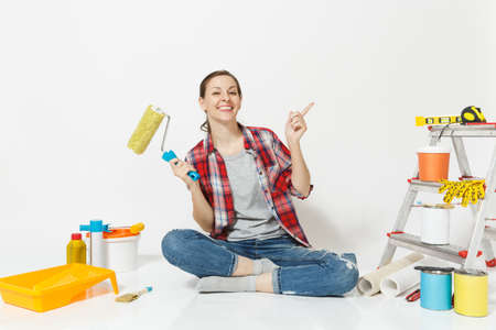 Woman in casual clothes sitting on floor with paint roller, instruments for renovation apartment isolated on white background. Wallpaper, accessories for gluing, painting tools. Repair home concept Stock Photo