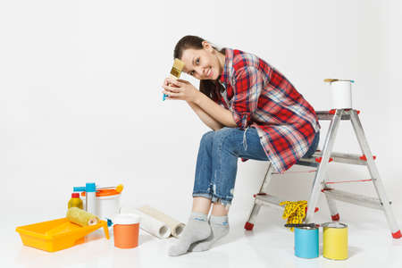 Pretty woman in casual clothes sitting on ladder with brush, instruments for renovation apartment isolated on white background. Wallpaper, accessories for gluing, painting tools. Repair home concept Reklamní fotografie