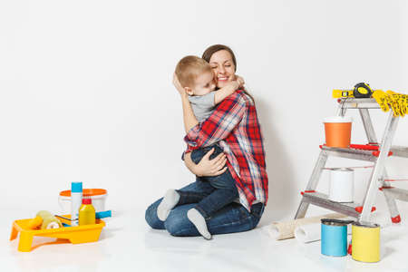 Mother hug her small son. Instruments for renovation apartment room isolated on white background.