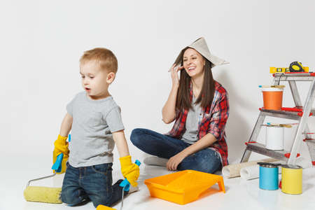 Mother and small son with instruments for renovation apartment room isolated on white background. Wallpaper, gluing accessories, painting tools. Boy woman repairing home. Parenthood childhood concept