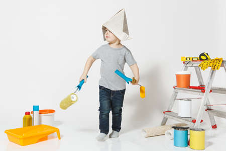 Little cute boy in newspaper hat with instruments for renovation apartment room isolated on white background. Wallpaper, gluing accessories, painting tools. Repair home. Parenthood, childhood concept Reklamní fotografie