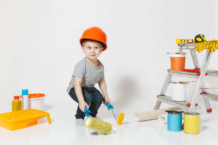 Little boy in orange protective helmet with instruments for renovation apartment isolated on white background. Wallpaper, gluing accessories, painting tools. Repair home. Parenthood childhood concept Reklamní fotografie