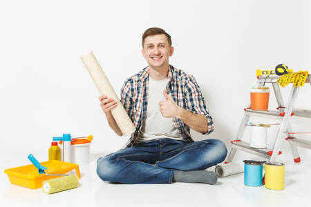 Smiling man showing thumbs up, sitting on floor with roll of wallpaper, instruments for renovation apartment room isolated on white background. Gluing accessories, painting tools. Repair home concept