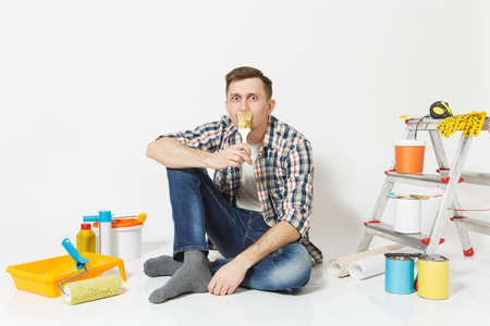 Smiling fun man sitting on floor with paint brush like mustache, instruments for renovation apartment isolated on white background. Wallpaper, gluing accessories, painting tools. Repair home concept