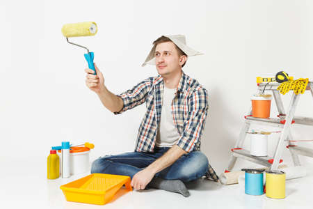 Man in newspaper hat sitting on floor, using paint roller, instruments for renovation apartment room isolated on white background. Wallpaper, gluing accessories, painting tools. Repair home concept Stock Photo