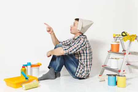 Young man in newspaper hat sitting on floor with instruments for renovation apartment room isolated on white background. Wallpaper, gluing accessories, painting tools. Repair home concept. Side view