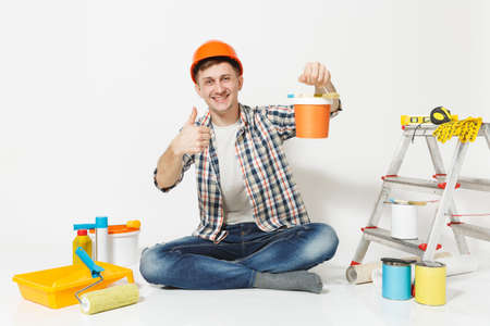 Man in orange protective helmet sitting on floor with paint can, instruments for renovation apartment isolated on white background. Wallpaper, gluing accessories, painting tools. Repair home concept Reklamní fotografie