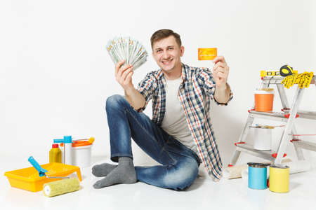 Young happy man holds bundle of dollars, cash money, cretit card sits on floor with instruments for renovation apartment isolated on white background. Wallpaper, painting tools. Repair home concept.