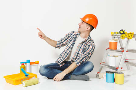 Man in orange protective helmet pointing index finger aside on copy space. Instruments for renovation apartment isolated on white background. Wallpaper, accessories, painting tools. Repair concept Archivio Fotografico