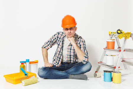 Serious man in orange protective helmet sitting on floor with instruments for renovation apartment room isolated on white background. Wallpaper gluing accessories, painting tools. Repair home concept