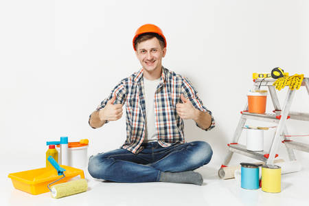 Man in orange protective helmet showing thumbs up, sitting on floor with instruments for renovation apartment isolated on white background. Wallpaper gluing accessories painting tools. Repair concept