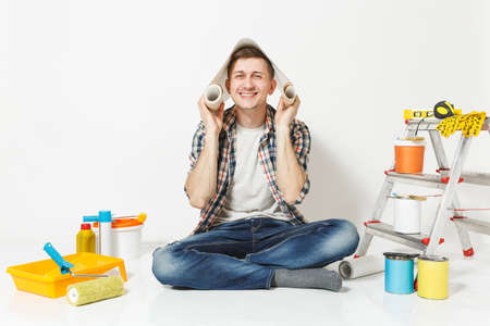 Fun young male sitting on floor with roll of wallpaper above head, instruments for renovation apartment room isolated on white background. Gluing accessories, painting tools. Repair home concept Reklamní fotografie