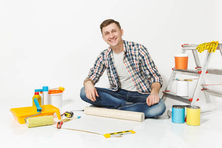 Young man sitting on floor with wallpaper roll, pencil, instruments for renovation apartment room isolated on white background. Wallpaper, gluing accessories, painting tools. Repair home concept Reklamní fotografie