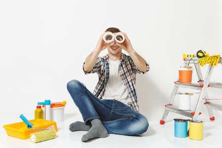 Fun male look through rolls of wallpaper as in binoculars, sit on floor, instruments for renovation apartment isolated on white background. Gluing accessories, painting tools. Repair home concept Reklamní fotografie