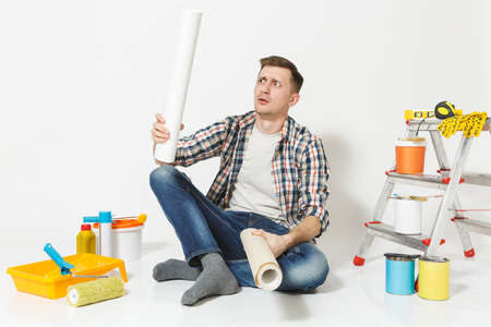 Confused annoyed tired man sitting on floor with rolls of wallpaper, instruments for renovation apartment room isolated on white background. Gluing accessories, painting tools. Repair home concept Reklamní fotografie