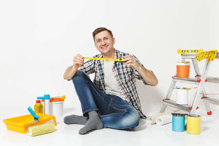 Man in casual clothes sitting on floor with measure tape, instruments for renovation apartment room isolated on white background. Wallpaper, gluing accessories, painting tools. Repair home concept